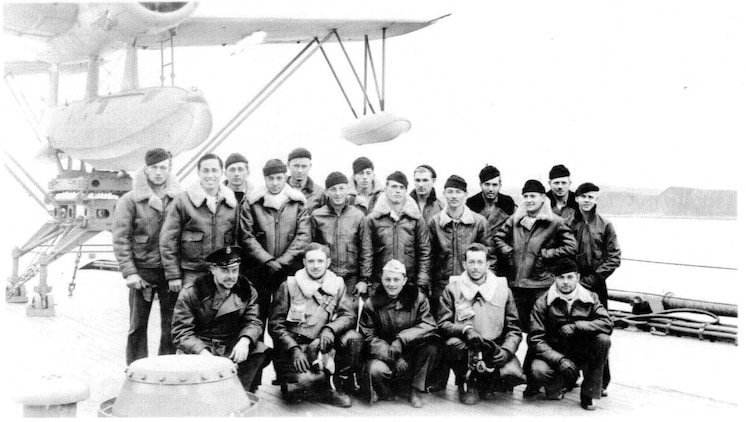 Aviation Radioman 2nd Class Harrison D. Miller (back-center) aboard the flight deck of the USS New Mexico (BB-40) with fellow flight crews for OS2N-1 ?Kingfisher? observation/scout float planes.  Miller later received the Distinguished Flying Cross for his heroic actions on 31 January 1944 when U.S. forces invaded Kwajalein Atoll. At 1522 local time, his plane was hit by enemy anti-aircraft fire from Ebeye Island, an enemy float plane base at the time. The Kingfisher suffered serious damage and was forced to make an emergency water landing in the lagoon due to high octane aviation fuel leaking into the bilges in the cockpit, filling it with fuel fumes presenting a critical fire hazard.  The pilot, Navy Lieutenant Forney O. Fuqua was mortally wounded by the enemy fire and instructed the Miller, in the rear cockpit of the Kingfisher, to bail out.  Miller elected to stay with the plane and to attempt a water landing himself from the rear cockpit.  With no prior flying experience, no flight instruments and only an emergency control stick in the rear cockpit, he successfully made a water landing from the back seat of the Kingfisher.  After landing, Miller got out of the rear cockpit onto the wing and made his way to the front cockpit and turned off the Kingfisher?s engine and started to unbuckle the pilot?s parachute and harness; but before he could get him unbuckled, the plane capsized due to the loss of the outboard pontoons during the landing.  Miller made numerous attempts to rescue the pilot and remove him from the cockpit, diving under the gasoline covered waters but was unsuccessful.