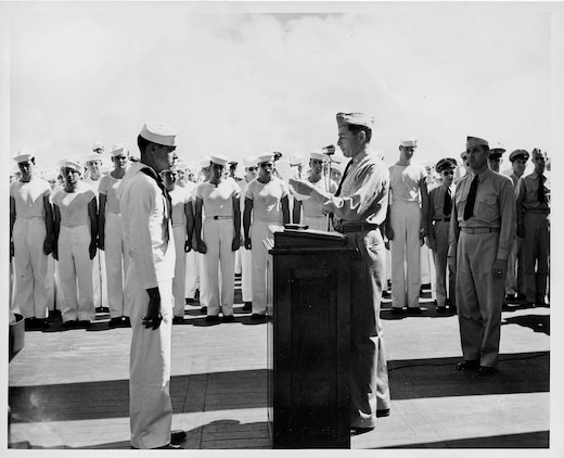 Aviation Radioman 2nd Class Harrison D. Miller receives the Distinguished Flying Cross for his heroic actions on 31 January 1944 when U.S. forces invaded Kwajalein Atoll. At 1522 local time, an OS2N-1 ?Kingfisher? observation/scout float plane from the USS New Mexico (BB-40) was hit by enemy anti-aircraft fire from Ebeye Island, an enemy float plane base at the time.  The Kingfisher suffered serious damage and was forced to make an emergency water landing in the lagoon due to high octane aviation fuel leaking into the bilges in the cockpit, filling it with fuel fumes presenting a critical fire hazard.  The pilot, Navy Lieutenant Forney O. Fuqua was mortally wounded by the enemy fire and instructed the Radioman in the rear cockpit of the Kingfisher, Harrison Miller, to bail out.  Miller elected to stay with the plane and to attempt a water landing himself from the rear cockpit.  With no prior flying experience, no flight instruments and only an emergency control stick in the rear cockpit, he successfully made a water landing from the back seat of the Kingfisher.  After landing, Miller got out of the rear cockpit onto the wing and made his way to the front cockpit and turned off the Kingfisher?s engine and started to unbuckle the pilot?s parachute and harness; but before he could get him unbuckled, the plane capsized due to the loss of the outboard pontoons during the landing.  Miller made numerous attempts to rescue the pilot and remove him from the cockpit, diving under the gasoline covered waters but was unsuccessful.