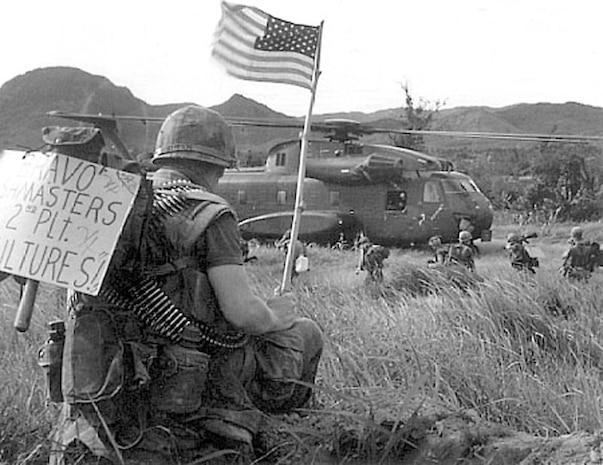 "A Marine from 2nd Platoon ""Vultures,"" of Bravo Company ""Bushmasters,"" bares the Stars and Stripes while others from his unit board a CH-53A Sea Stallion with Marine Heavy Helicopter Squadron 463 in Vietnam in 1967. Initially a World War II bomber squadron, HMH-463, Marine Aircraft Group 16 (Reinforced), 3rd Marine Aircraft Wing, flew the first CH-53s in Vietnam with the main mission of providing assault support transport, which they still do today."