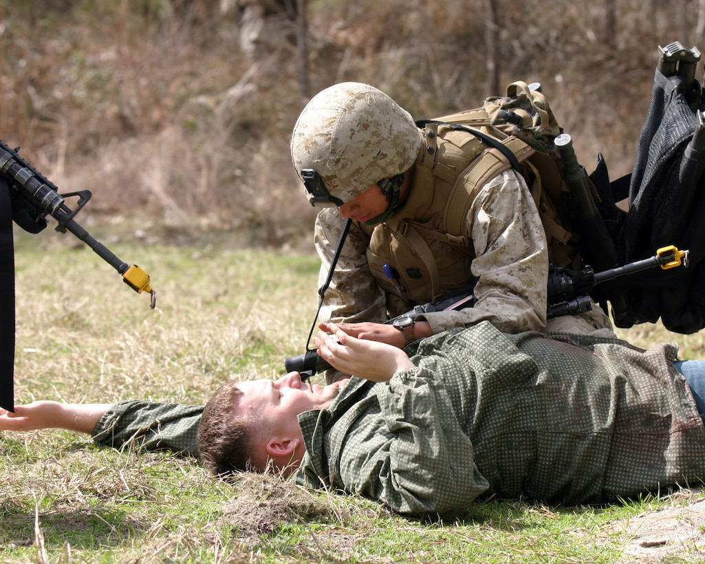 Hospital Man Miguel Montoya, the platoon's corps-man for Light Armored Reconnaissance platoon (LAR), gives medical attention to an injured pilot during a Tactical Recovery of Aircraft and Personnel course held aboard Camp Lejeune, NC, March 7, 2007. Part of the five-day course, involved the LAR Marines executing mock TRAP missions in different scenarios over various terrains with life-size dummies and role players. The Marines and Sailors of the LAR, an attachment of the Weapons Company, Battalion Landing Team, 3/8 is scheduled to deploy with the 22d Marine Expeditionary Unit later this year. (U.S. Marine Corps photo by Sgt. Ezekiel R. Kitandwe)