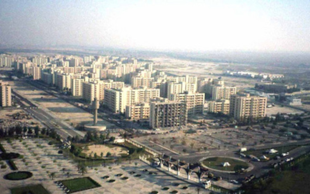 The bomb damaged building which housed U.S. military personnel and served as the headquarters for the U.S. Air Force's 4404th Wing (Provisional), Southwest Asia is in the foreground of this aerial photograph taken of the Khobar Towers complex near King Abdul Aziz Air Base, Dhahran, Saudi Arabia on June 29, 1996. The explosion of a fuel truck set off by terrorists at 2:55 p.m. EDT, Tuesday, June 25, 1996, outside the northern fence of the facility killed 19 and injured over 260. U.S. and Saudi law enforcement and military personnel are combing through the blast area searching for clues to the identity of the terrorists.