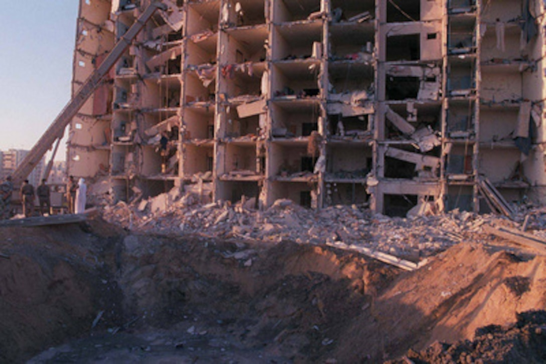 U.S. and Saudi military personnel survey the damage to Khobar Towers caused by the explosion of a fuel truck outside the northern fence of the facility on King Abdul Aziz Air Base near Dhahran, Saudi Arabia, at 2:55 p.m. EDT, Tuesday, June 25, 1996. Several buildings were damaged and there were numerous U.S. casualties. The latest information from Dhahran indicates that 19 people are dead and 64 people are hospitalized. Additionally, over 200 have been treated for injuries and released. The facility houses U.S. service members and serves as the headquarters for the U.S. Air Force's 4404th Wing (Provisional), Southwest Asia.