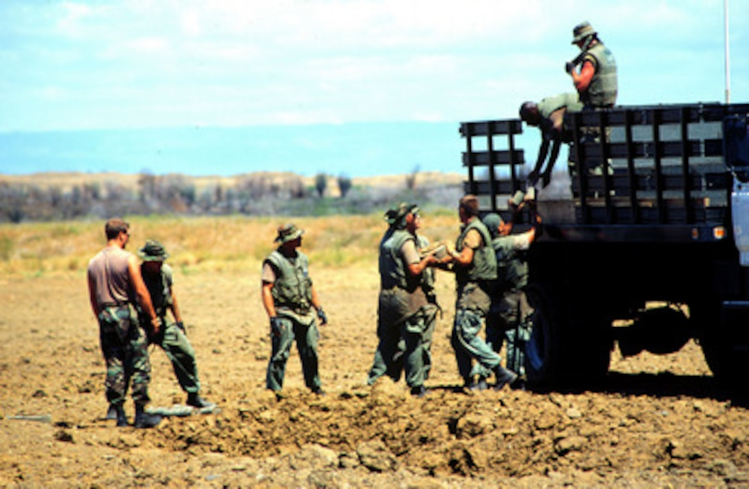 Marine Barracks Minefield Maintenance personnel unload deactivated anti-tank and anti-personnel land mines for destruction at a demolition site on Naval Station Guantanamo Bay, Cuba, in this March 18, 1997, file photo. Anti-personnel and anti-tank land mines on the U.S. side of the fence separating Communist Cuba and the U.S. Naval Base at Guantanamo Bay are being removed in accordance with the Presidential Order of May 16, 1996. Approximately 50,000 land mines were placed in the buffer zone between Communist Cuba and Guantanamo Bay beginning in 1961 as a result of the Cold War. The land mines are being replaced by motion and sound sensors to detect any incursion onto the base.