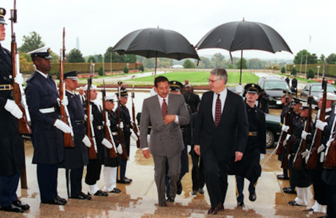 Deputy Secretary of Defense John H. Hamre (right) escorts Commander, Saudi Arabian Air Force Gen. Turki bin Nasser (left) through an honor cordon into the Pentagon on Oct. 20, 1999.