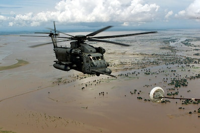 Picture of a Pave Low helicopter refueling while flying over flooded plains in Mozambique, 2000.