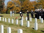Sailors from the USS Cole (DDG 67) pay their respects to recently buried Cole crew members at Arlington National Cemetery on Nov. 11, 2000. Cole sailors were invited to take part in Veterans Day receptions and ceremonies at the White House and Arlington Cemetery. The Arleigh Burke class destroyer was the target of a suspected terrorist attack in the port of Aden, Yemen, on Oct. 12, 2000, during a scheduled refueling. The attack killed 17 crew members and injured 39 others.