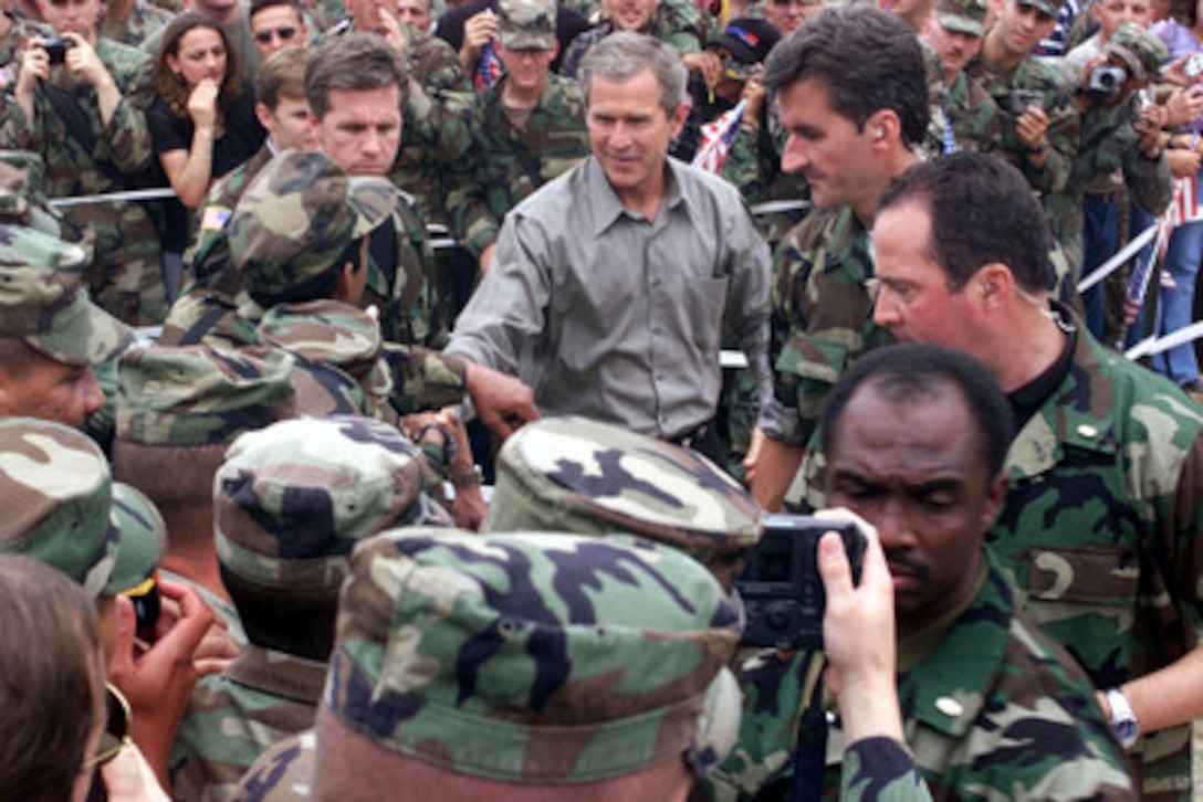 President George W. Bush shakes hands with American soldiers during his visit to Camp Bondsteel in Kosovo on July 24, 2001. Bush is visiting the Task Force Falcon soldiers to show support for the troops in Kosovo. The president signed the fiscal year 2001 Emergency Supplemental Appropriations legislation which contains $1.9 billion for military pay, benefits and health care among other categories during his visit.