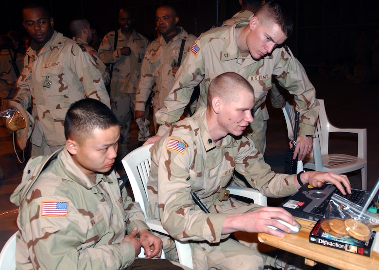 AVIANO AIR BASE, Italy -- Army soldiers from Fort Lee, Va., play a computer game while on a layover here awaiting transportation to a forward-deployed location. (U.S. Air Force photo by Airman 1st Class Nichole Adamowicz)
