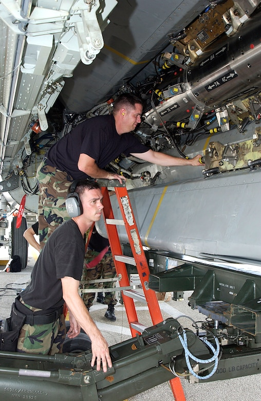 ANDERSEN AIR FORCE BASE, Guam  --  Staff Sgts. John Beldin (top) and Landon Favors, B-52 Stratofortress weapons loaders, prepare an air-launched cruise missle for loading on a B-52 here March 20.  Aircraft and support troops from the 2nd Bomb Wing at Barksdale Air Force Base, La., are deployed as part of the 7th Air Expeditionary Wing.  (U.S. Air Force photo by Senior Airman Christina M. Rumsey)