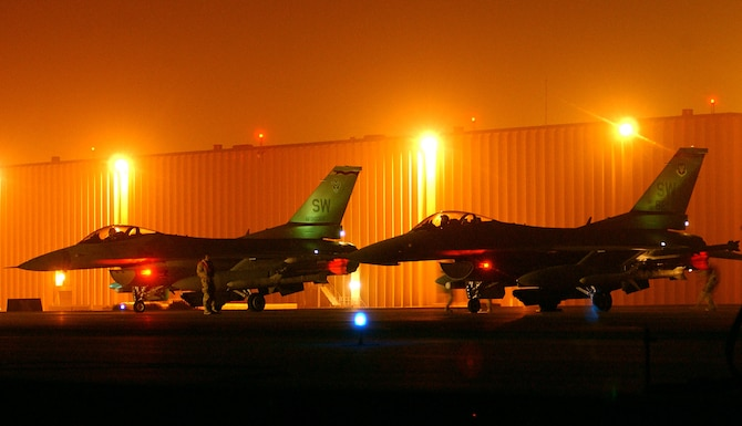"""OPERATION IRAQI FREEDOM --  F-16 Fighting Falcons wait on the """"hot ramp"""" at a forward-deployed location while maintenance crews ready the weapons for a night mission March 21.  The F-16s are from the 20th Fighter Wing at  Shaw Air Force Base, S.C., and they are flying Operation Iraqi Freedom missions for the 363rd Expeditionary Fighter Squadron. (U.S. Air Force photo by Staff Sgt. Matthew Hannen)"""