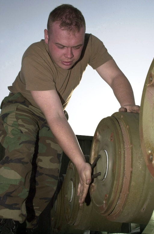 """OPERATION IRAQI FEEDOM -- Senior Airman Josh Vader, from the 5th Expeditionary Maintenance Squadron's munitions flight, prepares an MK-84 """"dumb bomb"""" for transition to a GBU-31 Joint Direct Attack Munition """"smart bomb."""" Four components are added to the MK-84 turning it into a precision Global Positioning System-guided weapon.  (U.S. Air Force photo by Staff Sgt. Kristina Barrett)"""