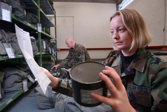 RHEIN-MAIN AIR BASE, Germany -- Senior Airman Anke Dzincielewski inspects the dates on gas mask canisters to ensure they are current.  Dzincielewski grew up in East Germany and remembers life before the Berlin Wall came down.  She is deployed here from Ellsworth Air Force Base, S.D.  (U.S. Air Force photo by Master Sgt. Keith Reed)