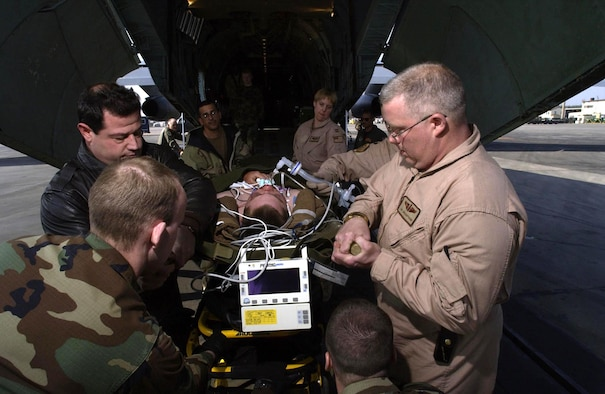 RAMSTEIN AIR BASE, Germany -- Tech. Sgt. John Schiffhauer (right) of the 932nd Aeromedical Evacuation Squadron at Scott Air Force Base, Ill., and members of the 86th Aeromedical Staging Facility here unload a wounded soldier from a C-141 Starlifter on March 24. Twelve soldiers wounded during Operation Iraqi Freedom were evacuated to Germany for additional medical treatment. (U.S. Air Force photo by Tech. Sgt. Justin D. Pyle)