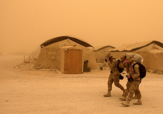 OPERATION IRAQI FREEDOM -- Airmen struggle to walk through a heavy sand storm at this forward-deployed air base March 26.  Troops supporting Operation Iraqi Freedom are battling sand storms throughout the Middle Eastern region.  (U.S. Air Force photo by Staff Sgt. Derrick C. Goode)