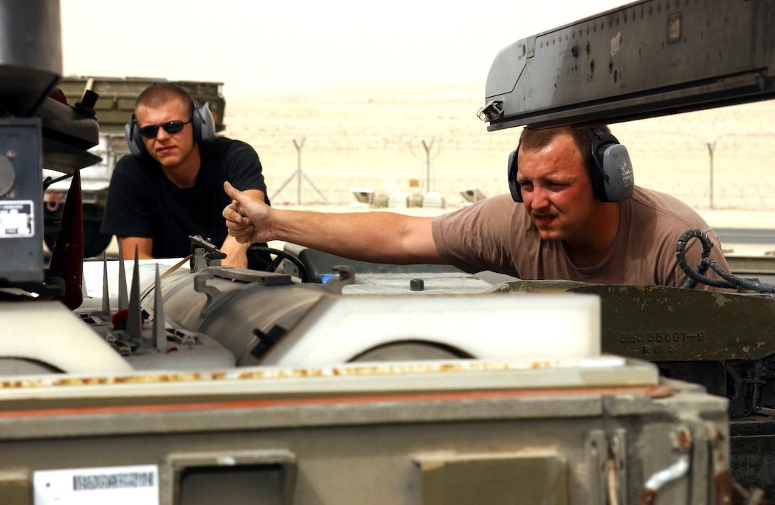 OPERATION IRAQI FREEDOM -- Airman 1st Class Michael Gucciardi drives the jammer while Staff Sgt. David Ross gives hand signals indicating which direction to move the missile while loading on a F-16CJ at a forward deployed location in Southwest Asia.(U.S. Air Force photo by Master Sgt. Terry L. Blevins)