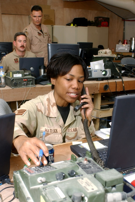 OPERATION IRAQI FREEDOM -- Staff Sgt. Selena Matlock tracks aircraft take off and landing times at the Coalition Operations Center, ensuring Air Tasking Orders are updated.  In the background, Lt. Col. Joseph Justice (standing) and Maj. David Wright, Coalition Operations Center directors, coordinate the flying schedule.  All are assigned to the 379th Air Expeditionary Wing at a deployed location. (U.S. Air Force photo by Master Sgt. Terry Blevins)