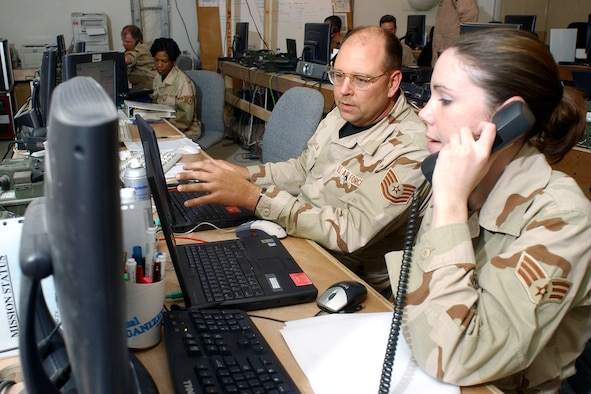 OPERATION IRAQI FREEDOM -- Tech. Sgt. Raymond Saylor and Senior Airman Kristina Degracia, Coalition Operations Center members, update sortie mission and flight filing.  Both are assigned to the 379 Air Expeditionary Wing at a deployed location. (U.S. Air Force by Master Sgt. Terry Blevins)