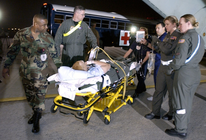 ANDREWS Air Force Base, Md. -- Crew members of the 491st Expeditionary Air Medical Evacuation Squadron carry one of 13 U.S. coalition force members wounded in the war in Iraq off of a C-141 Starlifter to a waiting ambulance here March 28, 2003.  The 13 patients, made up of two airmen, one sailor, four Marines and six soldiers, are the first wounded in the war in Iraq to arrive in the United States. They were flown in from Landstuhl Hospital, Ramstein Air Base, Germany, for treatment at Walter Reed Army Medical Center in Washington, D.C. and Bethesda Naval Medical Center in Rockville, Md.  The 491st EAMES is made up of Air Force Reservists from McGuire Air Force Base, N.J., and McChord Air Force Base, Wash.,  (U.S. Air Force photo by Tech. Sgt. Jim Varhegyi)