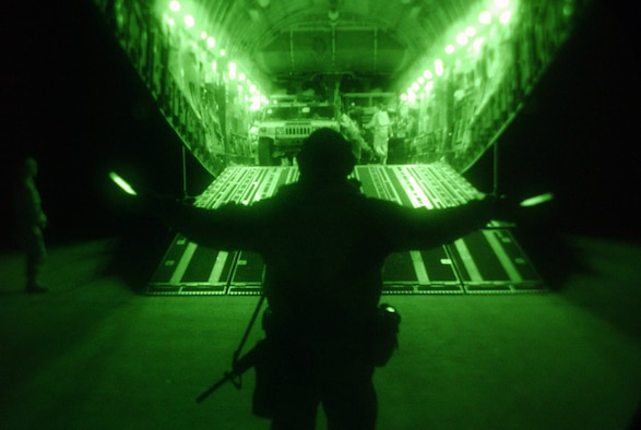 OPERATION IRAQI FREEDOM -- Master Sgt. Gerritt McCrory of the 86th Expeditionary Contingency Response Group marshals cargo and people from a C-17 Globemaster III aircraft during night operations March 30 at an airfield in northern Iraq.  (U.S. Air Force photo by Tech. Sgt. Rich Puckett)