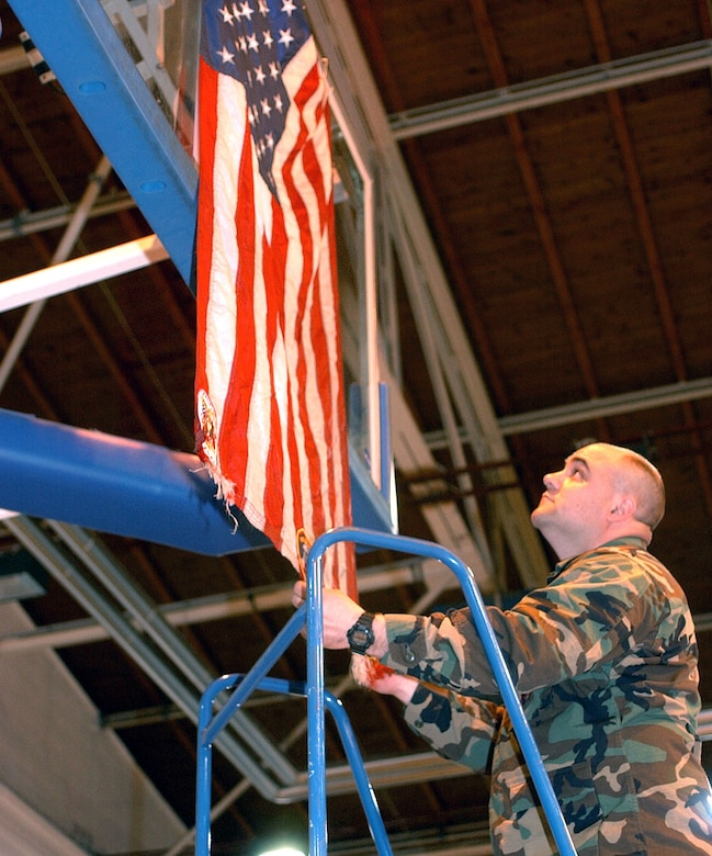 RAMSTEIN AIR BASE, Germany -- Capt. Eric Szillus, a clinical nurse with the 514th Aeromedical Staging Squadron from McGuire AFB, hangs an American flag flown at Ground Zero in the Ramstein Southside Fitness Center.  (U.S. Air Force photo by Airman 1st Class Melissa Maraj)