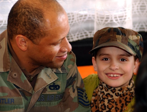 OPERATION IRAQI FREEDOM -- Tech. Sgt. Terrance Butler shares his hat with a Bulgarian child April 2. Butler is currently assigned to the 409th Air Expeditionary Group at Camp Sarafovo, Bulgaria. More than 40 children from two orphanages in nearby Burgas toured the camp and entertained the deployed troops. (U.S. Air Force photo by Master Sgt. Dave Ahlschwede)