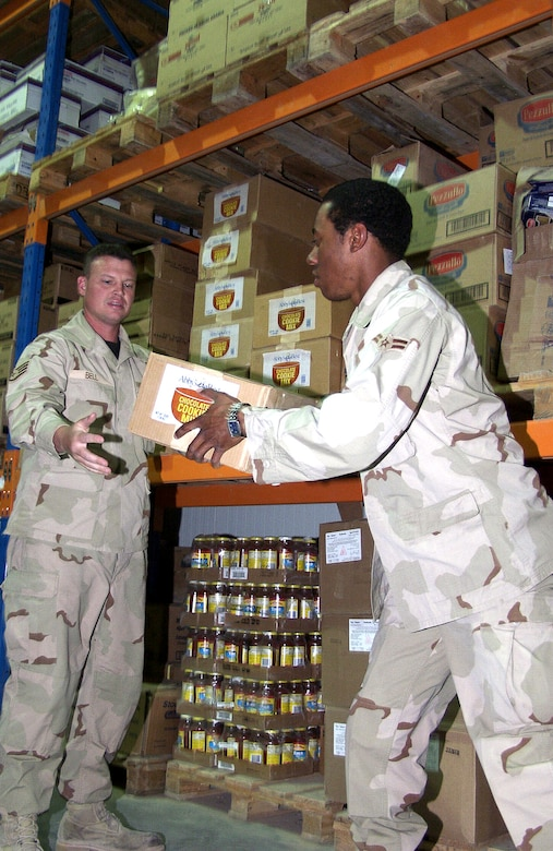OPERATION IRAQI FREEDOM – Staff Sgt. Steven Bell and Airman 1st Class Idris Royal stock the dry storage warehouse. Approximately $2,500,000 of subsistence is received and prepared monthly in support of the base population. Operation Iraqi Freedom is the multinational coalition effort to liberate the Iraqi people, eliminate Iraq's weapons of mass destruction and end the regime of Saddam Hussein. (U.S. Air Force photo)