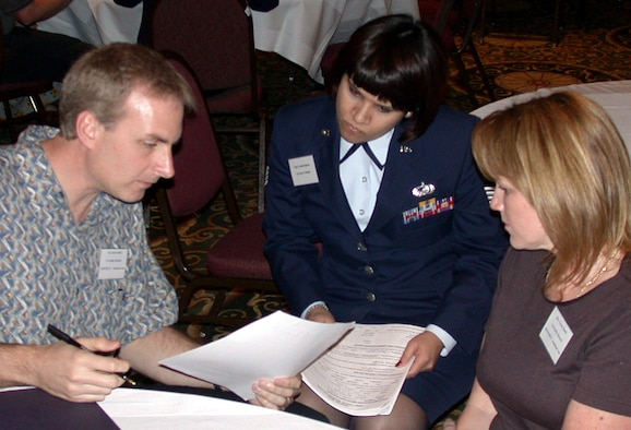 HOUSTON -- Staff Sgt. Cynthia Iniguez from the casualty office at the Air Force Personnel Center at Randolph Air Force Base, Texas, speaks with family members at a recent meeting for families of servicemembers missing from past wars.  More than 150 Texas families met in Houston with military representatives and officials from the Defense POW/Missing Personnel office, the agency responsible for oversight of the recovery process.  (U.S. Air Force photo by 1st Lt. Brandon Lingle)