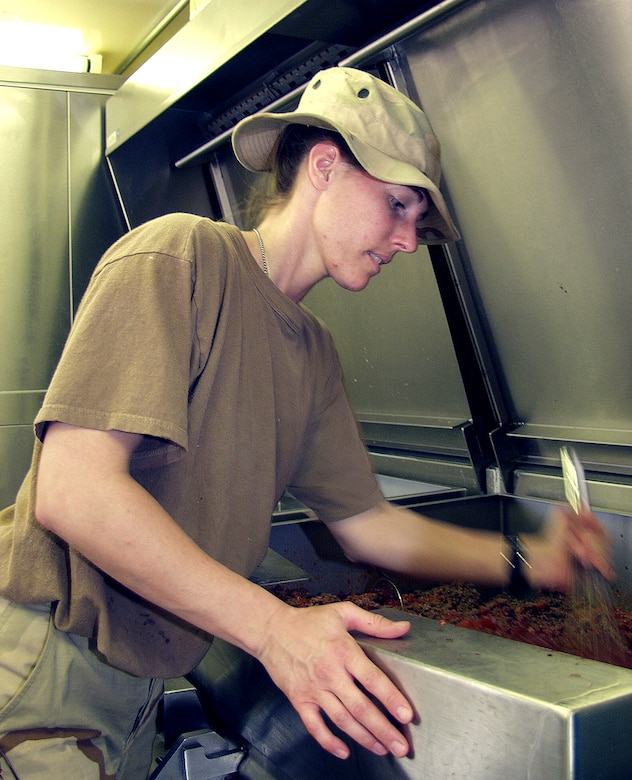 OPERATION IRAQI FREEDOM –- Inside a containerized deployable kitchen, Staff Sgt. Theresa Schaible mixes ingredients for Sloppy Joes. The 386th Expeditionary Services Squadron food services members feed thousands of military members several times daily. The kitchen always stays open, even in Alarm conditions, so that food will be available afterward. Operation Iraqi Freedom is the multinational coalition effort to liberate the Iraqi people, eliminate Iraq's weapons of mass destruction and end the regime of Saddam Hussein. (U.S. Air Force photo)