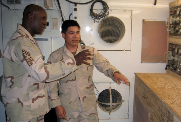 OPERATION IRAQI FREEDOM -- Airman 1st Class Manuel Hernandez shows Chief Master Sgt. Mack Williams the inside of the 444th Air Expeditionary Group's power plant during the chief's visit to a desert air base supporting Operation Iraqi Freedom on April 6.  The U.S. Central Command Air Forces command chief master sergeant travels regularly throughout the region. Hernandez is a power plant production apprentice from Moody Air Force Base, Ga.  (U.S. Air Force photo by Master Sgt. Charles Ramey)