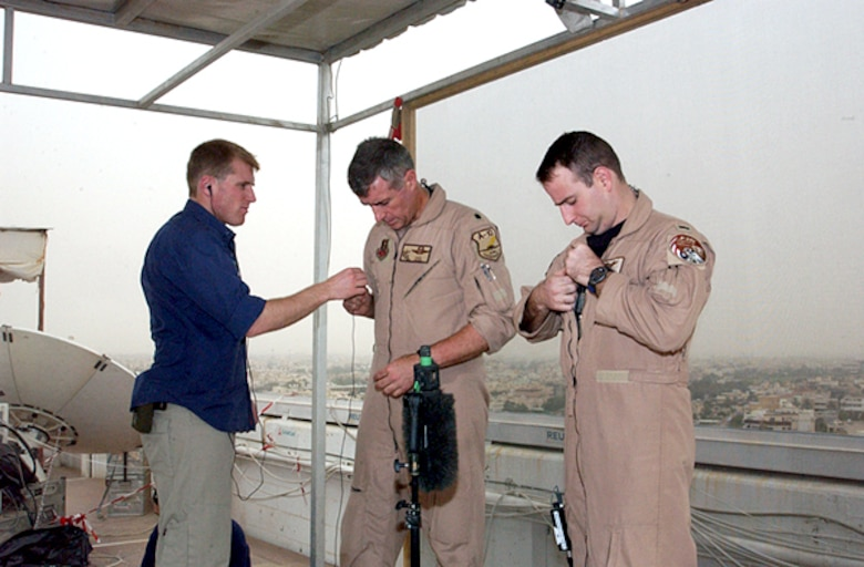 OPERATION IRAQI FREEDOM -- A sound technician assists Lt. Col. Mike Webb and 1st Lt. Chad Martin, 332nd Air Expeditionary Wing fighter pilots, with their microphones prior to a live satellite feed from Kuwait City. (U.S. Air Force Photo by Master Sgt. Stefan Alford)