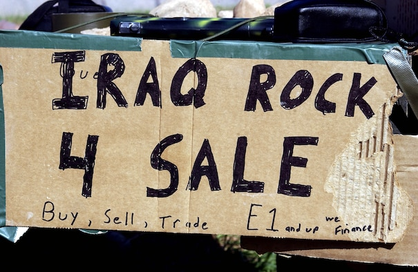 OPERATION IRAQI FREEDOM -- The rock merchants' sign to passing aircrews at Bashur Airfield in northern Iraq tells it all.  Three airmen from the 86th Expeditionary Contingency Response Group at Ramstein Air Base, Germany, are selling rocks to passing aircrews as a way to let off steam from their jobs on the flightline.  (U.S. Air Force photo by Master Sgt. Keith Reed)