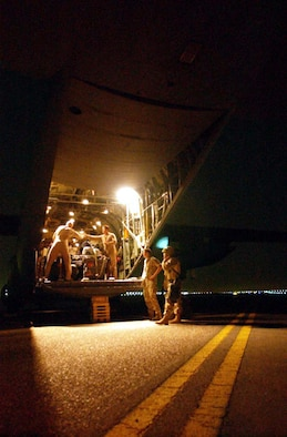 OPERATION IRAQI FREEDOM -- U.S. Air Force personnel secure humanitarian pallets onto a C-130 Hercules that will be flown to Baghdad to help Iraqi citizens in need. The flight marked the first of flights delivering supplies that are being donated from the people of Kuwait as part of a coordinated effort with the U.S. military to transport and deliver aid to the people of Iraq in support of Operation Iraqi Freedom. (U.S. Navy photo by PH1(SW) Arlo Abrahamson)
