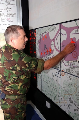 OPERATION IRAQI FREEDOM -- Royal Air Force Sgt. Dave Brumby, movement controller, arranges aircraft silhouettes on a map of the airfield parking plan.  401st Air Expeditionary Wing command post personnel are working side-by-side with their British counterparts supporting Operation Iraqi Freedom.  (U.S. Air Force photo by Airman 1st Class Melisa Kelly).