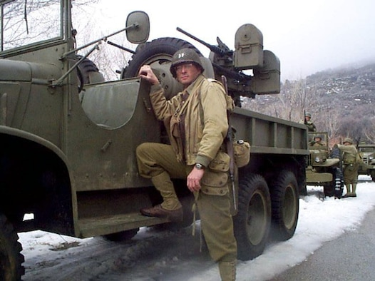 "SCHRIEVER AIR FORCE BASE, Colo. (AFPN) -- Maj. Allen Maj. Allen Vickrey stands beside a vintage World War II artillery jeep on the set of ""Saints of War.""  He plays an Army artillery officer taken as a prisoner of war in the movie scheduled for release this fall.  (Courtesy photo)"