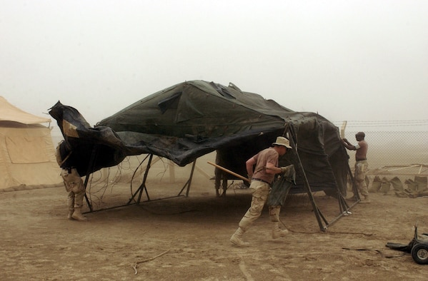 OPERATION IRAQI FREEDOM - Airmen from the 5th Combat Communications Group pitch in to set up a tent during a sandstorm at Tallil Air Base in southern Iraq on April 16.  The 5th CCG deployed from Robins Air Force Base, Ga., to Tallil recently.  (U.S. Air Force photo by Master Sgt. Terry L. Blevins)