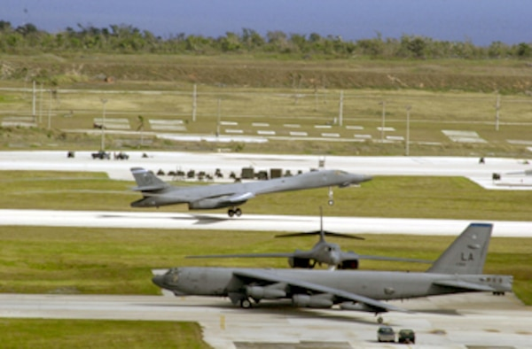ANDERSEN AIR FORCE BASE, Guam -- A B-1B Lancer takes off as a B-52 Stratofortress taxies past, readying for take-off here during last day of surges April 2.  (U.S. Air Force photo by Staff Sgt. Charlene M. Franken)