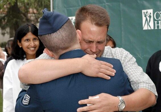 DUARTE, Calif. -- Cancer survivor Gregg Smith hugs Tech. Sgt. Daniel MacDonald, his bone marrow donor.  MacDonald donated bone marrow to Smith on Oct 16, 2001, but only met him recently.  (Courtesy photo by Bob Riha Jr.)