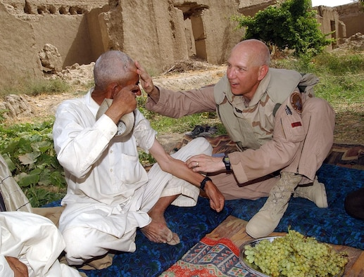 JAMADAAR, Afghanistan -- Ghulanhaider (left), an elder here, shows his scars from fighting with the Taliban to Col. Bill Busby, 455th Expeditionary Operations Group commander.  Ghulanhaider fought the Taliban and other terrorist groups before coalition forces arrived.  He has received multiple injuries from mortar fire and bullets.  (U.S. Air Force photo by Staff Sgt. Russell Wicke)