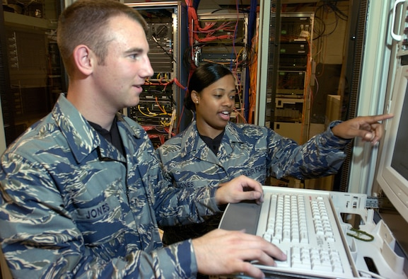 BOLLING AIR FORCE BASE, D.C. (AFPN) -- Airman 1st Class Jonathan Besko (left) and Senior Airman Brandi Wyatt, both with the 11th Communication Squadron here, try out the Air Force test utility uniform in a computer server room.  The blue, gray and green tiger-stripe camouflage ensemble includes many new features intended to increase functionality while providing a distinctive look for the 21st century airmen.  The uniforms will undergo wear-testing beginning in January.  Airmen from a cross section of Air Force career fields will provide feedback on the fit, durability and functionality of the proposed ensemble that will come in men's and women's cuts.  (U.S. Air Force photo by Master Sgt. Jim Varhegyi)