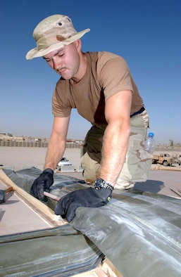 TALLIL AIR BASE, Iraq (AFPN) -- Senior Airman Jason Roush works on the roof of a small base exchange here.  He is assigned to the 332nd Expeditionary Civil Engineer Squadron.  (U.S. Air Force photo by Senior Airman Karolina Gmyrek)