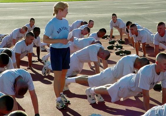 LACKLAND AIR FORCE BASE, Texas -- Staff Sgt. Dawn Adams (standing), a military training instructor with the 331st Training Squadron here, monitors trainees' pushups during physical readiness training.  New graduation standards for physical fitness take effect in basic training Oct. 12.  (Courtesy photo)