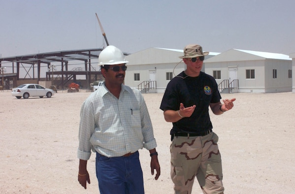 AL UDEID AIR BASE, Qatar -- First Lt. Steven Thomas (right) works closely with local contractors including N. Rajiv Shanker.  Expeditionary Village is being built to house at least 5,500 airmen at two per room.  Besides living quarters, construction projects include a new gymnasium, theater, chapel and base exchange with other amenities.  (U.S. Air Force photo by Master Sgt. John E. Lasky)