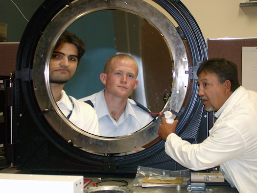 KIRTLAND AIR FORCE BASE, N.M. -- Dr. Richard Carreras aligns, pressurizes and cleans a prototype thin-film membrane mirror.  Reflected in the mirror are co-workers 2nd Lt. Ethan Holt, the film mirror project officer, and Nima Jamshidi, a Purdue University student employee.  (U.S. Air Force photo by Deb Mercurio)