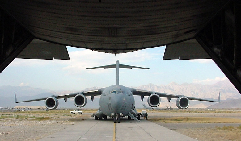 BAGRAM AIR BASE, Afghanistan -- A C-17 Globemaster III parks behind a C-130 Hercules on the flightline here Aug. 22.  C-17s are used extensively to deliver supplies and people to various forward-deployed locations throughout Southwest Asia.  (U.S. Air Force photo by Staff Sgt. Scott T. Sturkol)