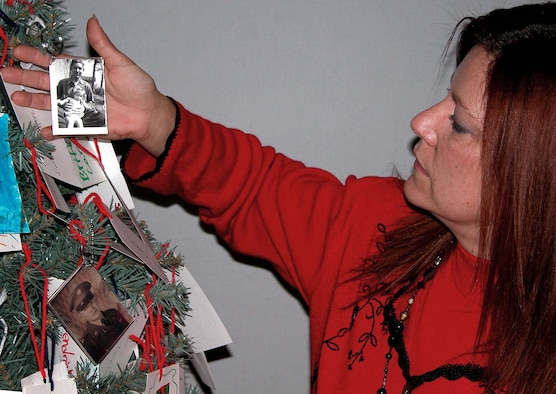 """WASHINGTON -- Retired Army Master Sgt. Peggy Marish-Boos, creator of the POW/MIA holiday tree, holds a picture of Army Cpl. Samuel C. """"Sam Jr."""" Harris who was lost during the Korean War on Nov. 27, 1950.  In the photo, 14-year-old Harris is shown holding his younger sister, Barbara Ann Harris, then 2.  (Department of Defense photo by Rudi Williams)"""