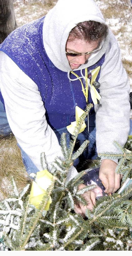 AUGUSTA, Maine -- Corey Folsom attaches a photo of a Maine servicemember on active duty for the war against terrorism to a giant Christmas wreath that he has had built beside the Maine National Guard headquarters here. (U.S. Army photo by Master Sgt. Angela Blevins)