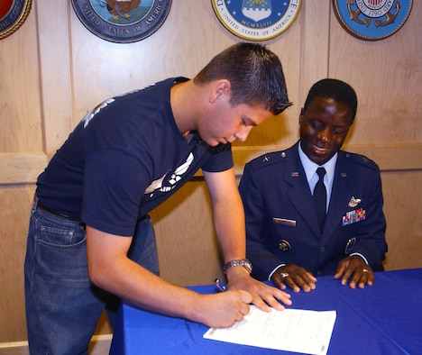 SAN ANTONIO -- Hector Baretto signs his Air Force enlistment contract, witnessed by Brig. Gen. Edward A. Rice Jr., Air Force Recruiting Service commander.  Baretto is the first Air Force 15-month enlistee under the National Call to Service program.  (U.S. Air Force photo by Angelica Delgado)