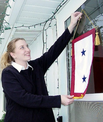 MINOT AIR FORCE BASE, N.D. -- Christa Wolfe, wife of 1st Lt. Marc Wolfe from the 741st Missile Squadron here, hangs a two-star service flag on her door. Christa's service flag honors her husband and her father, Lt. Col. Dennis McCarty, a chaplain at Little Rock Air Force Base, Ark. Service flags are hung during any period of war or hostilities in which the U.S. armed forces may be engaged. Each star represents a family member in the armed forces. (U.S. Air Force photo by Senior Airman Steve Grever)
