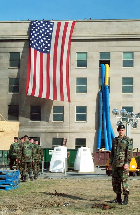 WASHINGTON -- Soldiers prepare to lower the garrison flag that draped the side of the Pentagon beside the impact site where terrorists crashed a hijacked airliner Sept. 11, 2001. The soldiers lowered and folded the flag Oct. 11, 2001. (U.S. Air Force photo by Jim Garamone)