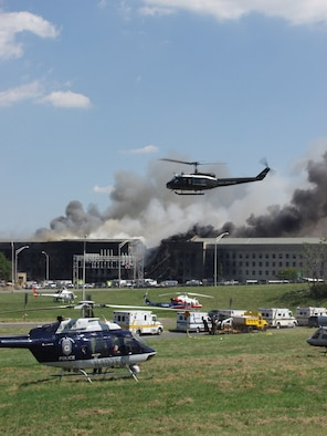 WASHINGTON -- Police helicopters and emergency ambulance crews stand by to aid injured workers following the crash of a hijacked commercial airliner into a section of the Pentagon.  Military and civilians helped transport injured people on litters to ambulances for treatment and transportation to hospitals. (U.S. Air Force photo by Staff Sgt. Gary Coppage)